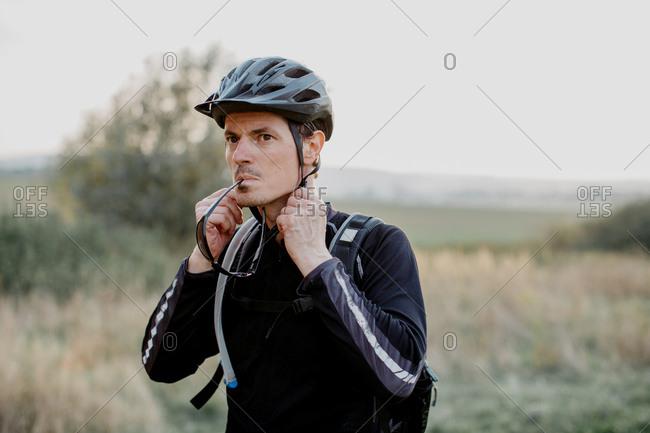 Male cyclist fastening helmet strap before setting off on bike trek