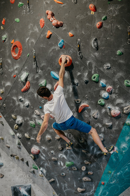 Back view of a male climber climbing up an artificial climbing wall