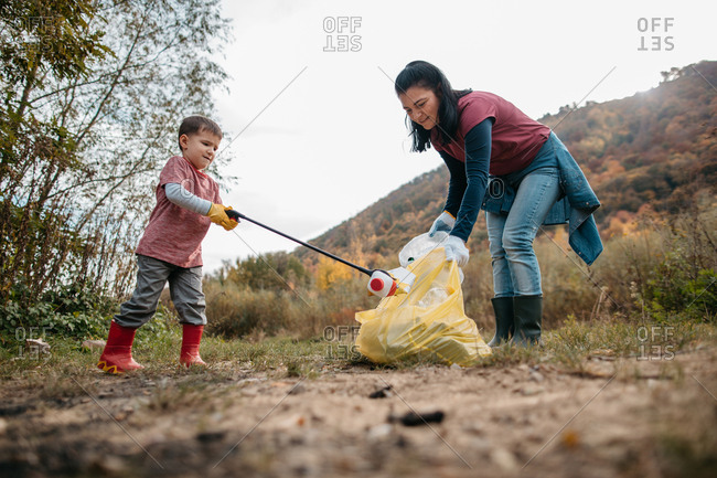 Ground angle shot of toddler boy cleaning up plastic trash in woods