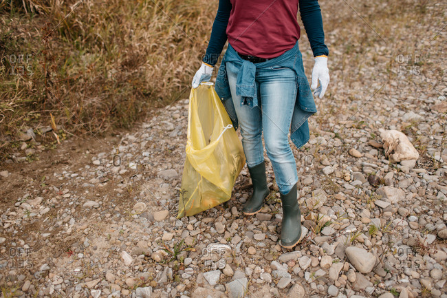 Cropped image of female volunteer carrying yellow plastic bag filled with rubbish