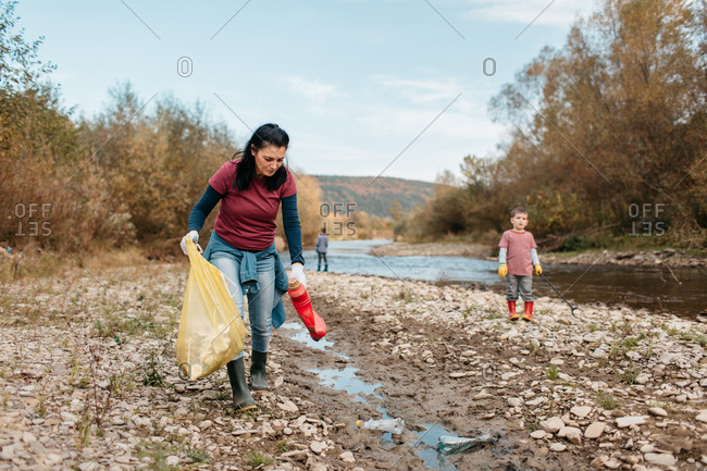 Female volunteer and her children picking up trash in nature