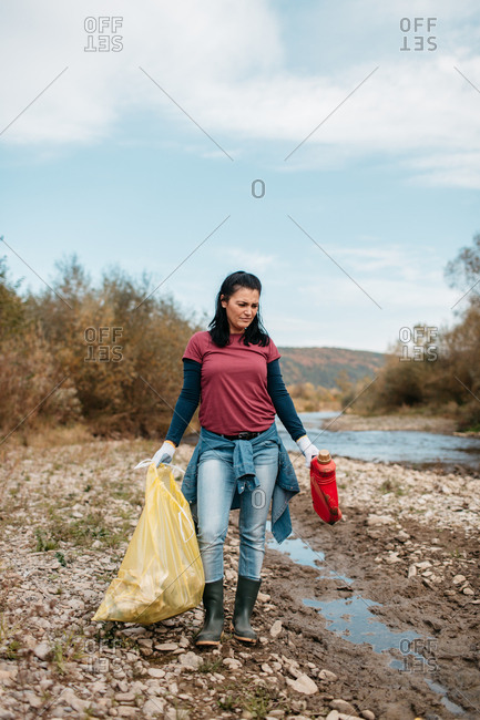 Portrait of female volunteer holding plastic bag filled with rubbish