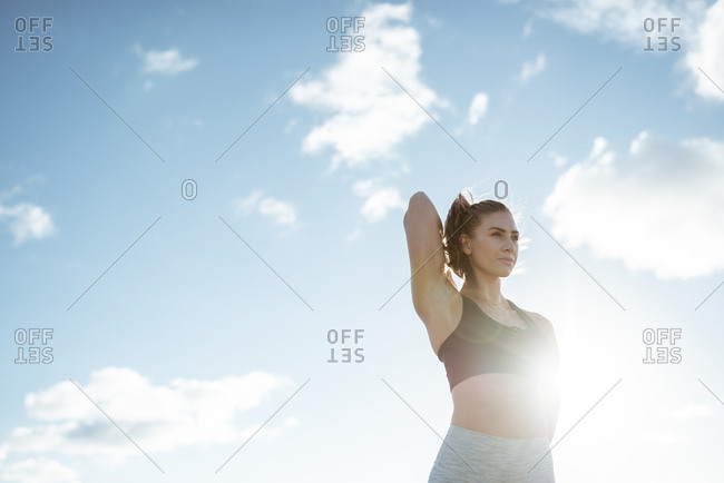 Low angle view of woman stretching her arms before workout in the countryside