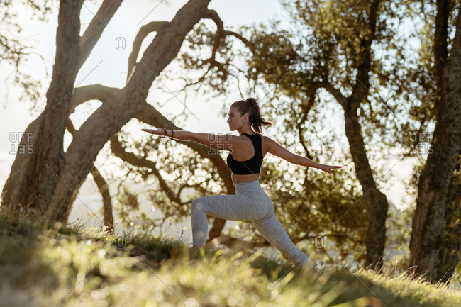 Young woman doing warrior yoga pose in the countryside