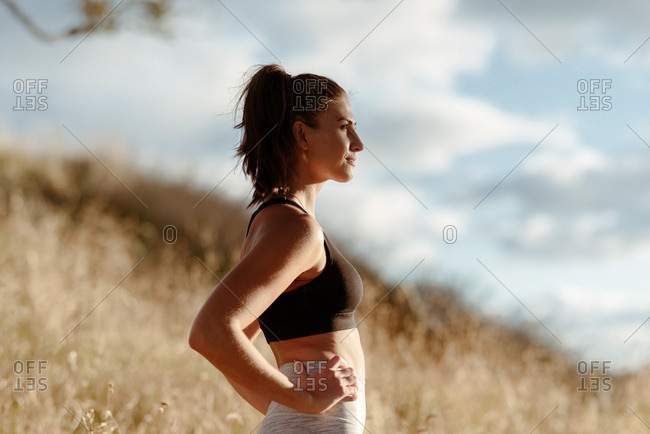 Profile view of young woman in workout clothes in the country