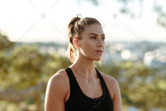 Young woman in workout clothes looking away