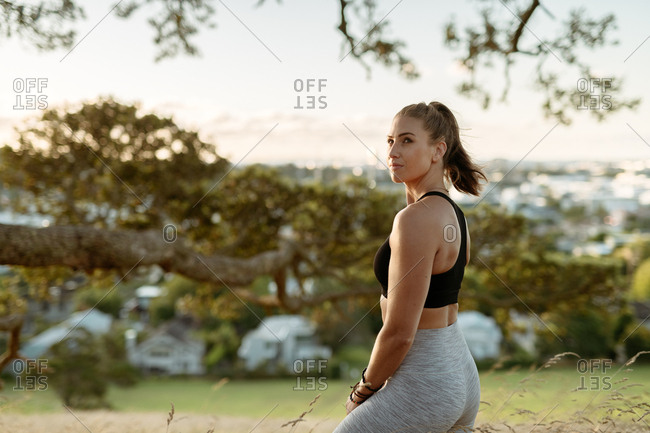 Young woman in workout clothes overlooking city from hilltop