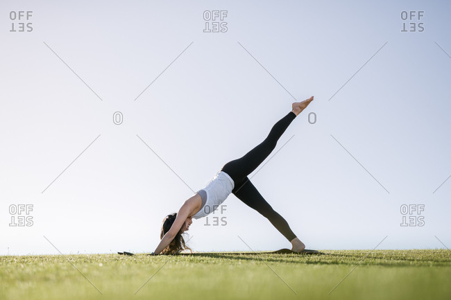 Young woman doing downward dog yoga pose in the countryside