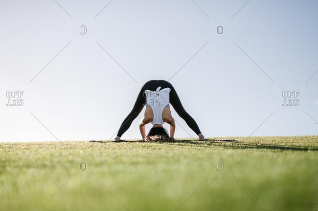 Woman doing wide-legged standing forward fold