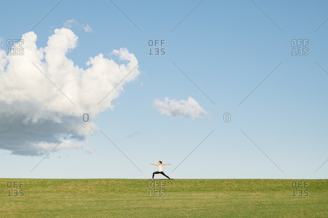 Young woman doing a yoga warrior pose in the distance