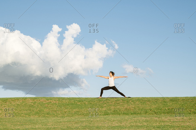 Young woman doing a yoga warrior pose on a grassy hill