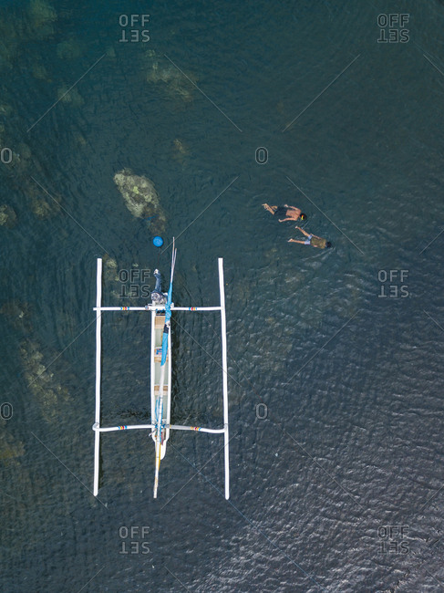 November 24, 2018: Asian boys  snorkeling in ocean- next to banca boat