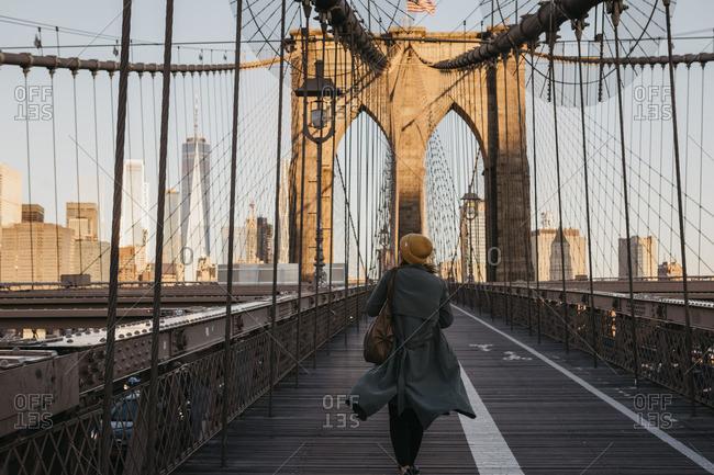 February 2, 2019: USA- New York- New York City- female tourist on Brooklyn Bridge in the morning light