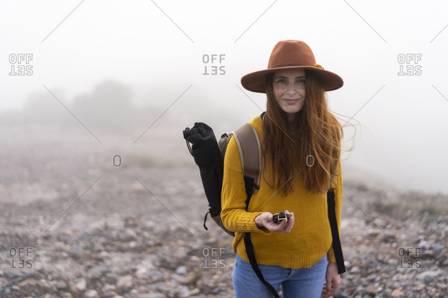 Woman hiking in the mountains- holding compass
