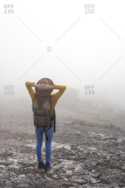 Woman with backpack- standing on mountain- looking at view