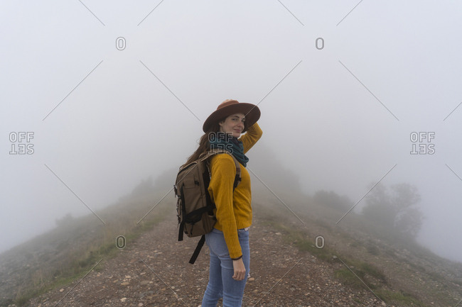 Woman hiking in the fog- standing on a mountain path