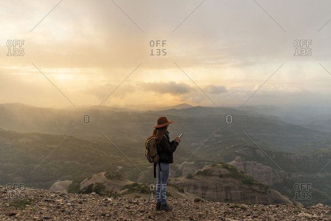 Woman with backpack- standing on mountain- looking at view- using smartphone
