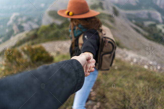 Woman with hat- standing on mountain- holding on to man's hand