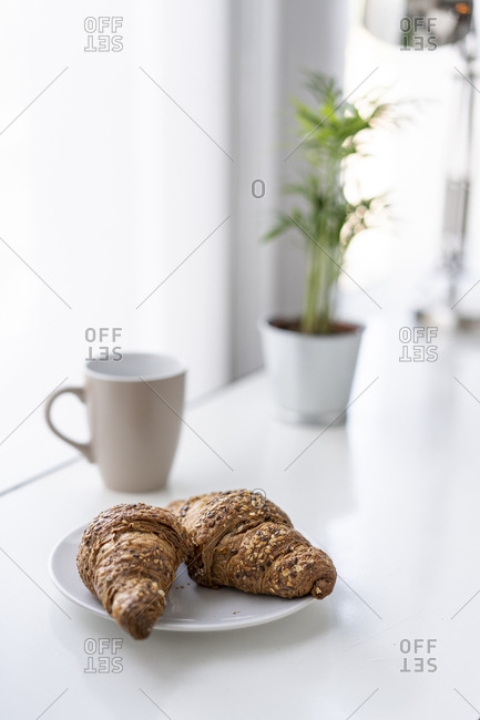 Croissants and a cup of coffee in an office