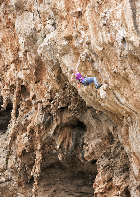 Greece- Kalymnos- woman climbing in rock wall