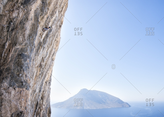 Greece- Kalymnos- climber in rock wall above the sea