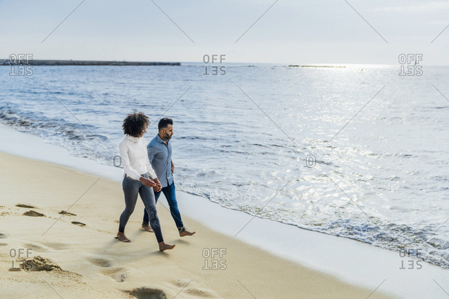 Spain- Barcelona- couple walking barefoot on the beach