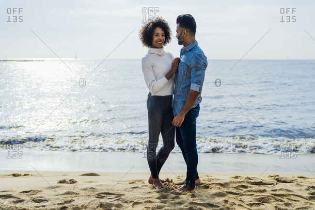 Spain- Barcelona- couple standing barefoot on the beach