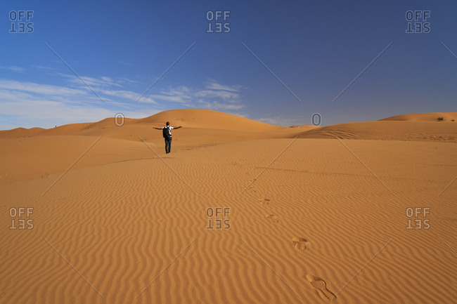 Morocco- back view of man with backpack standing on desert dune