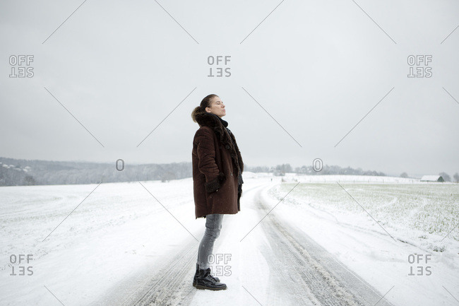 Mature woman standing on field way in winter
