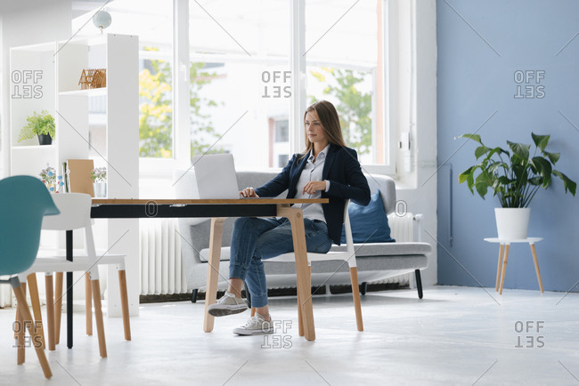 Young businesswoman sitting in office- using laptop