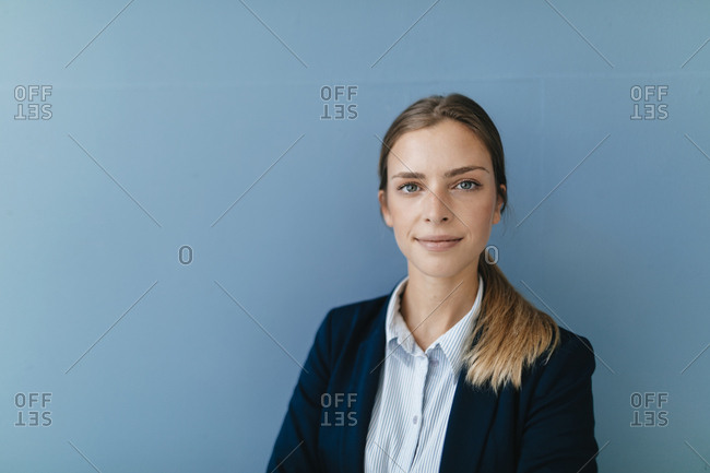 Portrait of a young businesswoman against blue background