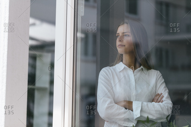Young businesswoman standing at the window- with arms crossed