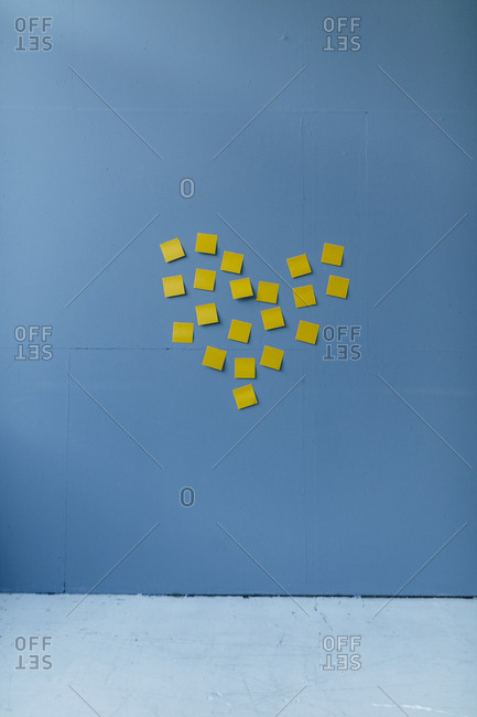 Heart-shape on a blue wall- made of yellow sticky notes