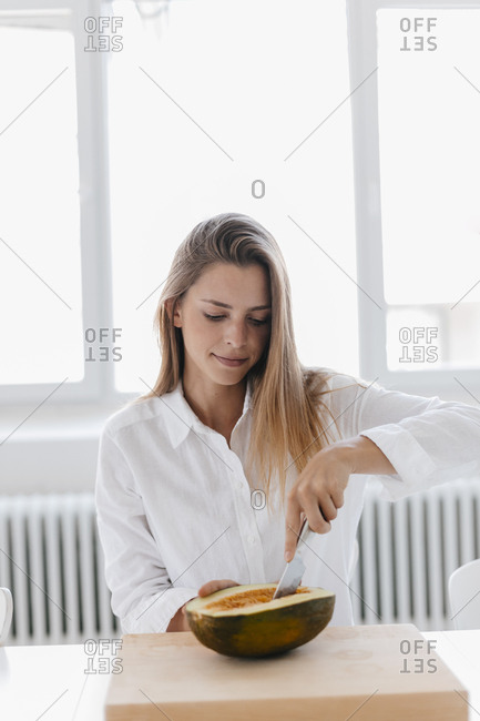 Young woman pitting half of a melon