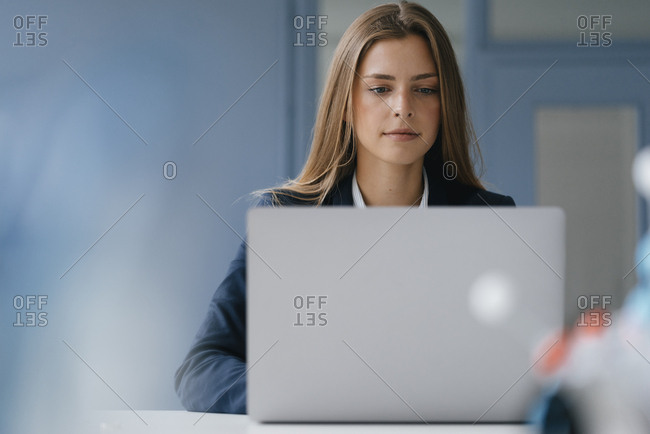 Portrait of a young businesswoman- working in office- using laptop