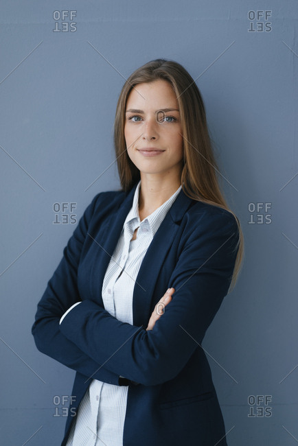 Portrait of a young businesswoman against blue background- with arms crossed