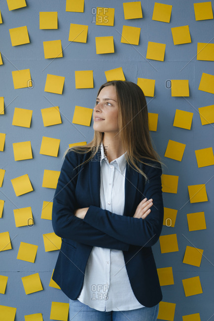 Yong businesswoman standing in front of wall- full of yellow sticky notes- with arms crossed