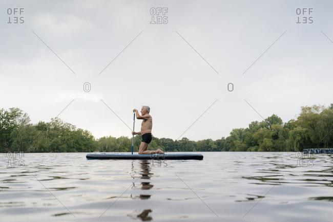 Senior man kneeling on SUP board