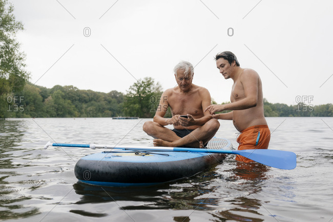 Older and younger man with SUP board on a lake using cell phone