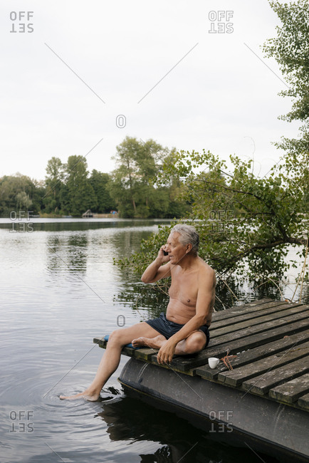 Senior man sitting on jetty at a lake talking on cell phone