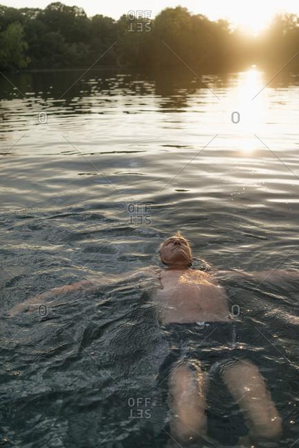 Senior man swimming in a lake at sunset