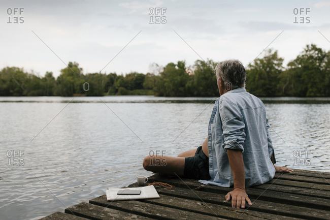 Senior man sitting on jetty at a lake