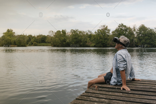 Senior man sitting on jetty at a lake wearing VR glasses