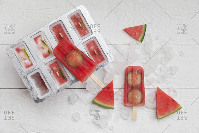 Homemade watermelon cucumber ice lollies on white ground