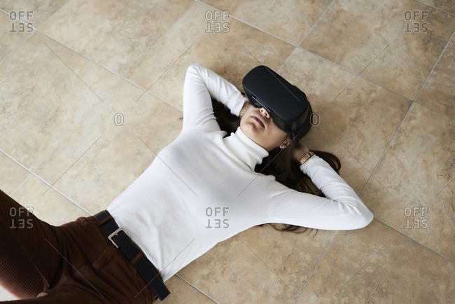 Young woman using virtual reality headsets lying on the floor at home