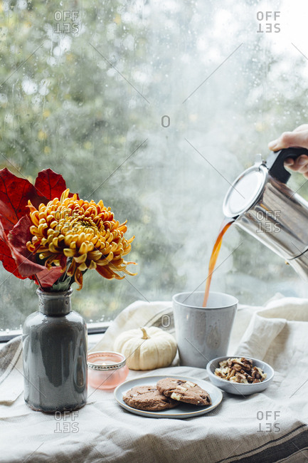 Woman's hand pouring hot coffee into a mug on rainy day