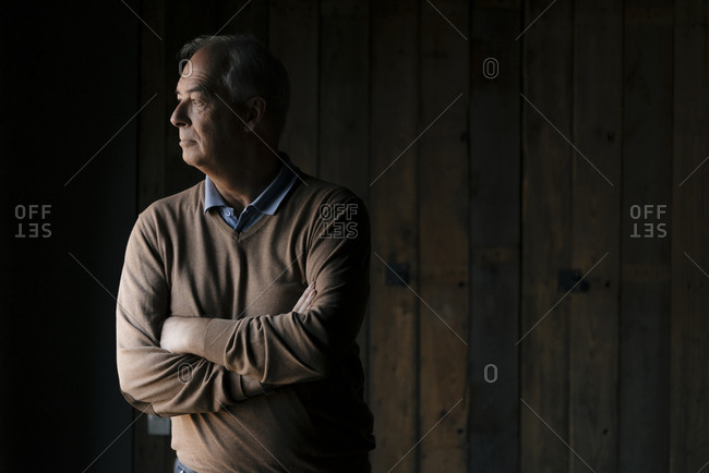 Serious senior businessman in front of wooden wall looking sideways