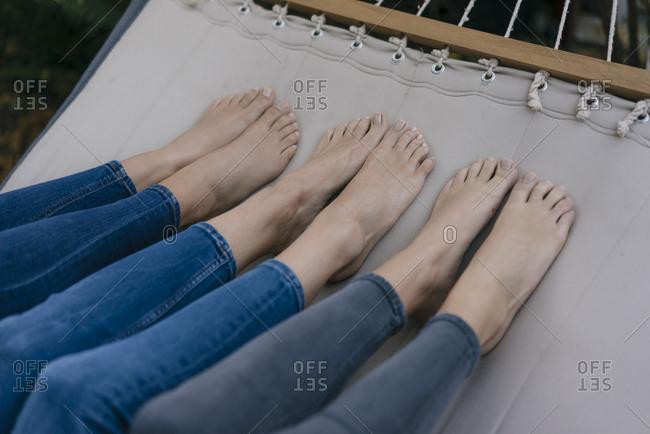 Feet of three females lying in hammock in garden