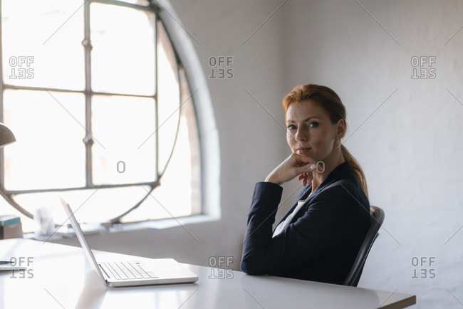 Portrait of businesswoman with laptop sitting at desk in office