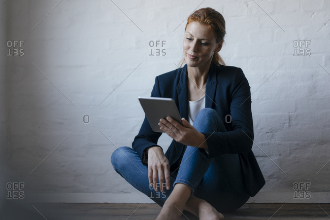 Bare feet businesswoman sitting on floor in office using tablet